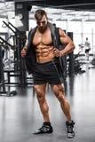 解决在健身房,强的男性赤裸躯干吸收的肌肉人 免版税库存照片