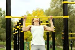 解决在室外健身房的年轻运动健身妇女做引体向上在日出 免版税库存照片