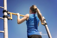 解决在室外健身房的年轻运动健身妇女做引体向上在日出 库存图片