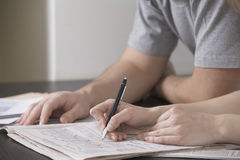 解决在报纸的夫妇Sudoku在书桌 库存图片