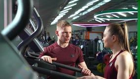 解决在机器的人们在健身房 与个人健身辅导员的妇女训练 股票视频