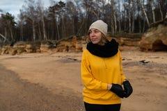 解决在海滩的愉快的体育和时尚恋人热心者穿明亮的黄色毛线衣和黑手套和盖帽 免版税库存图片