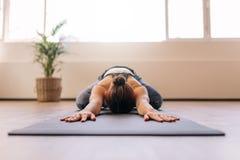 解决在瑜伽席子的健身妇女 免版税库存照片