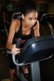 解决在转动的自行车的美国黑人的女孩在健身房 免版税库存照片