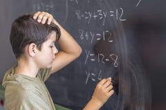 解决在黑板的男小学生一个问题 库存图片