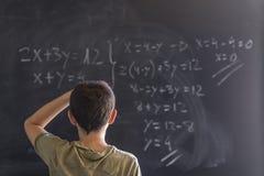 解决在黑板的男小学生一个问题 图库摄影