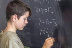 解决在黑板的男小学生一个问题 免版税图库摄影