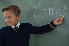 解决在黑板的男小学生算术惯例 免版税库存照片