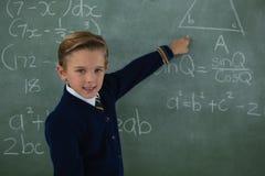 解决在黑板的男小学生算术惯例 图库摄影