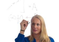 解决学员的美好的白肤金发的数学题 免版税库存照片