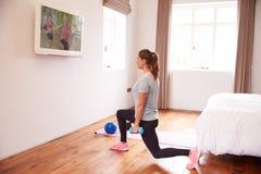 解决对在电视的健身DVD的妇女在卧室 免版税库存图片