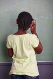 解决数学题的女孩在黑板 免版税库存图片