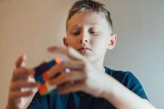 解决著名三维组合难题玩具的少年男孩在他的孩子室 免版税库存照片