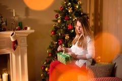解开圣诞节礼物假日树的女孩 免版税图库摄影