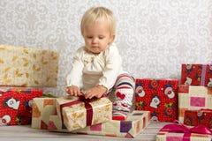 解开圣诞节礼物的小女孩 免版税图库摄影