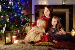 年轻解开圣诞节礼物的母亲和她的两个女儿由壁炉 免版税库存图片