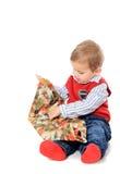 解开存在的逗人喜爱的小男孩 免版税图库摄影