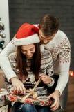 解开ch的红色圣诞老人帽子的愉快的微笑的深色的女朋友 免版税库存图片