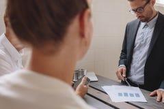 解释一个财政计划的男性执行委员对工友 库存图片