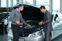 解释关于发动机的汽车推销员对顾客 免版税库存照片
