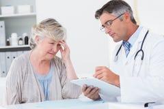 解释处方的医生对资深患者 库存图片