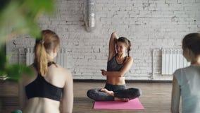 解释如何的专业瑜伽老师做胳膊锁和舒展胳膊和肩膀 她是讲话,微笑和 影视素材