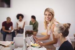 解释对女性同事的微笑的女实业家画象在办公室 库存照片