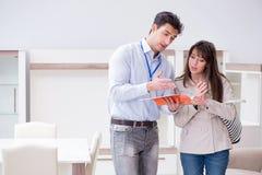 解释对妇女顾客的推销员在家具店 库存图片