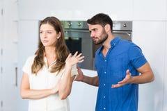 解释对翻倒妻子的人在厨房里 免版税库存照片