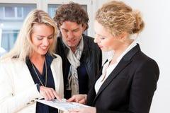 解释平面图的新地产商对夫妇 免版税库存照片
