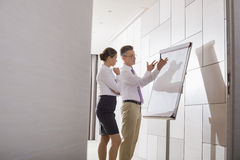 解释战略的商人对工友在办公室 库存图片