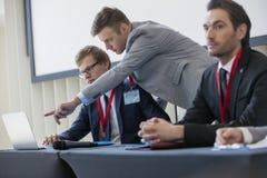解释战略的商人对膝上型计算机的同事在会议中心 免版税库存图片