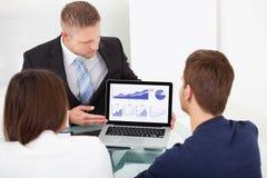 解释投资项目的顾问对夫妇 免版税库存图片