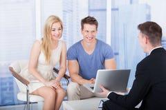 解释投资项目的财政顾问对在膝上型计算机的夫妇 库存照片
