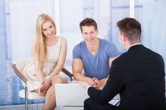 解释投资项目的财政顾问对在膝上型计算机的夫妇 免版税库存图片