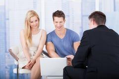 解释投资项目的财政顾问对在膝上型计算机的夫妇 免版税图库摄影