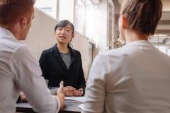 解释新的企业想法的女实业家对同事 免版税库存照片