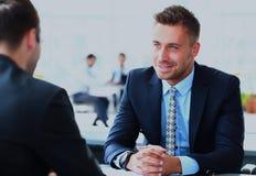 解释新的战略的精明的商人的图象对他的伙伴在会议上 免版税库存图片