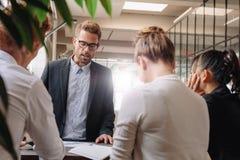 解释新的经营战略的商人对同事 免版税图库摄影