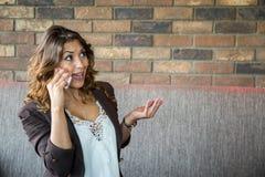 解释某事在电话的美丽的少妇 免版税图库摄影
