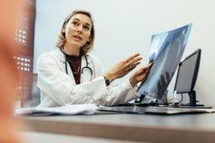 解释核对结果的医生对她的患者 库存图片