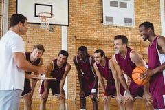 解释比赛计划的微笑的教练对蓝球运动员 免版税图库摄影