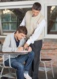 解释测试的老师对学生在教室 免版税库存图片