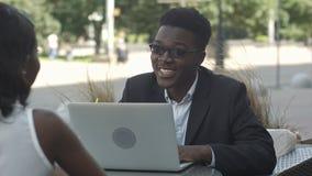 解释经营战略的非洲人对他的非洲女性同事,使用膝上型计算机在会议期间在咖啡馆 库存图片