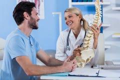 解释脊椎模型的生理治疗师对患者 库存照片