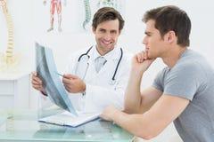 解释脊椎X-射线的微笑的医生对患者 库存照片