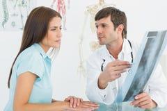 解释脊椎X-射线的医生对女性患者 库存照片