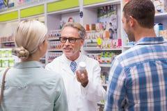 解释药片的资深药剂师对患者 库存照片