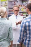 解释药片的资深药剂师对患者 免版税库存照片
