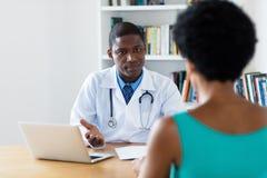 解释诊断的非裔美国人的医生对女性患者 免版税图库摄影